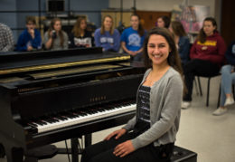 Anya Faruki sits at the piano in her music classroom.