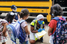 A school staff member writes down the name of a student, outside next to a school bus with other students nearby