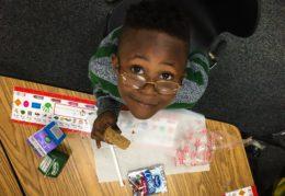 kindergarten student eating breakfast in the classroom'