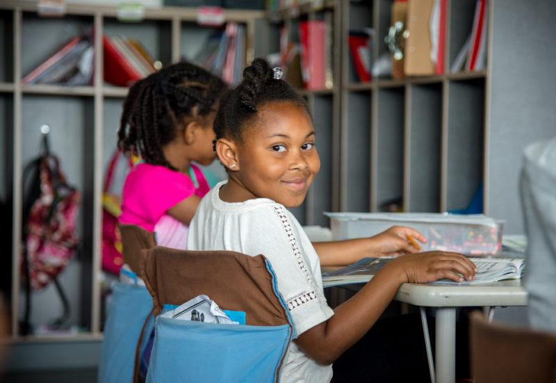 Smiling female elementary student at her desk