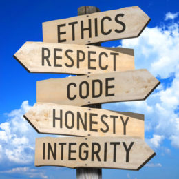 Directional signs on one post: ethics, respect, code, honesty, integrity
