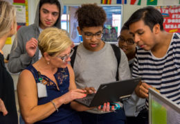 students with teacher and Chromebook