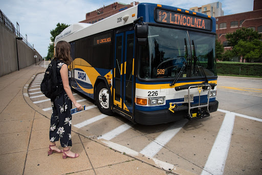 A woman awaits the doors of a DASH bus to open so she can board.