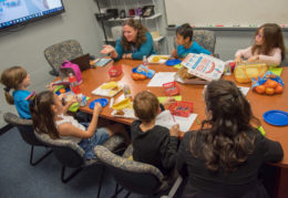 Students sit around a table and discuss qualities they'd like to see in their new school
