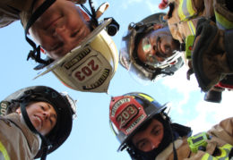"""a photo called """"Heroes All Around Me."""" A lot of students sent in photographs of firefighters, but Riley came up with the unique concept of having a circle of firefighters stand around him, looking down at him as he lay on the ground looking up, to take their photo from below"""