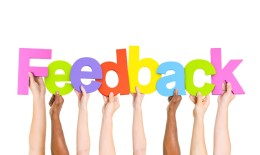 """Hands holding up colorful letters to spell the word """"feedback"""""""