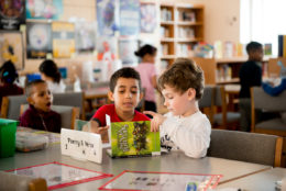 elementary school boys reading books at table