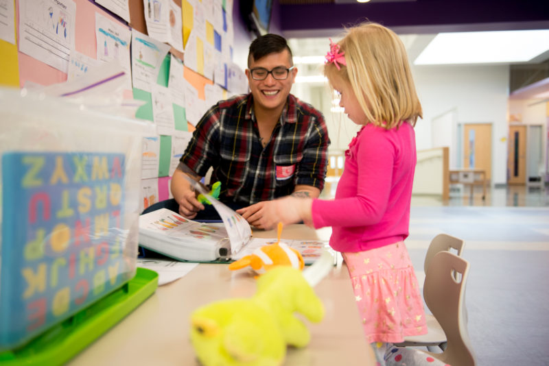 teacher working with elementary student