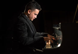 jonathan flores plays a grand piano on stage