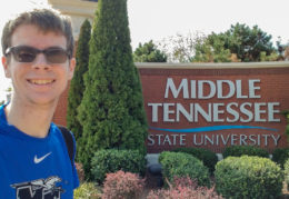 student standing in front of Middle Tennessee State University sign