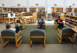 students reading books and using computer at GWMS library