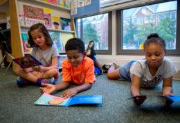three children reading books together
