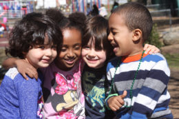 group of four pre-school aged kids hugging and smiling