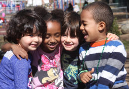 four preschool students hugging on a playground