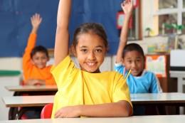 Girl in classrom raising hand