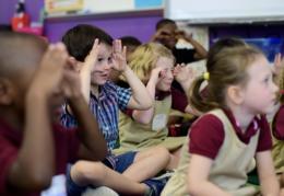 Kindergarteners sitting on the floor singing The Wheels on the Bus