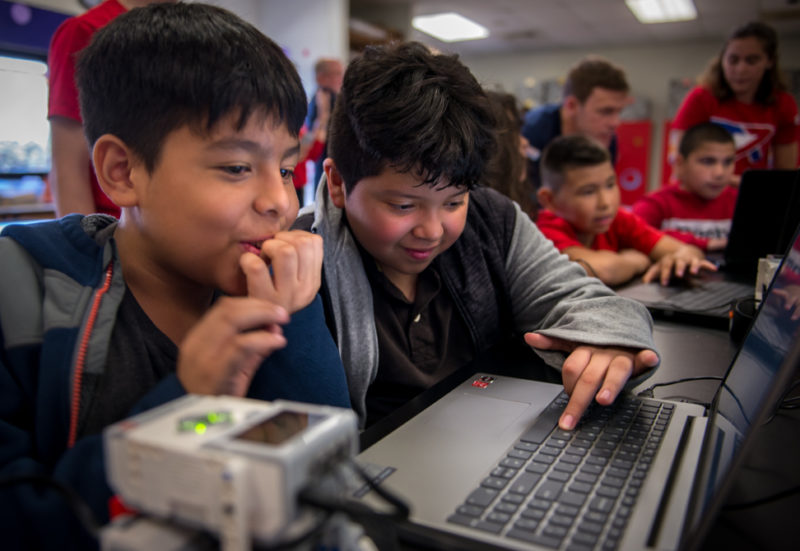 two young male students look at a computer and react to what they can make a small robot do