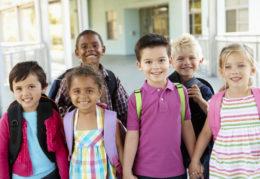 six smiling children holding hands