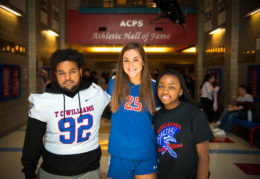 Three TC athletes stand together under the athletic hall of fame banner