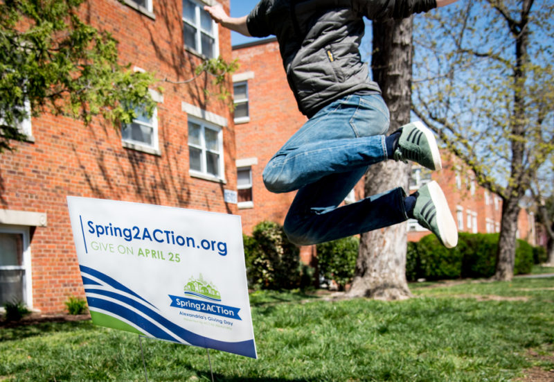 Person mid-air jumping above Spring2ACTion 2018 yardsign