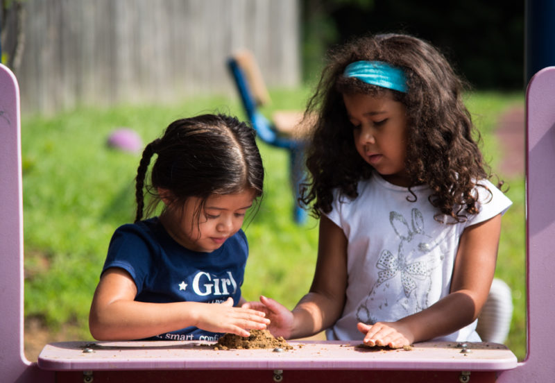 Two elementary school-aged girls playing with dirt on an outdoor surface