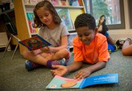 Two Tucker students reading on floor