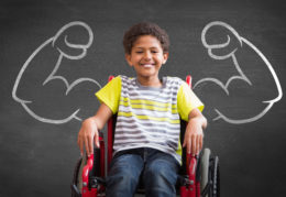 young boy in wheel chair with muscle arms
