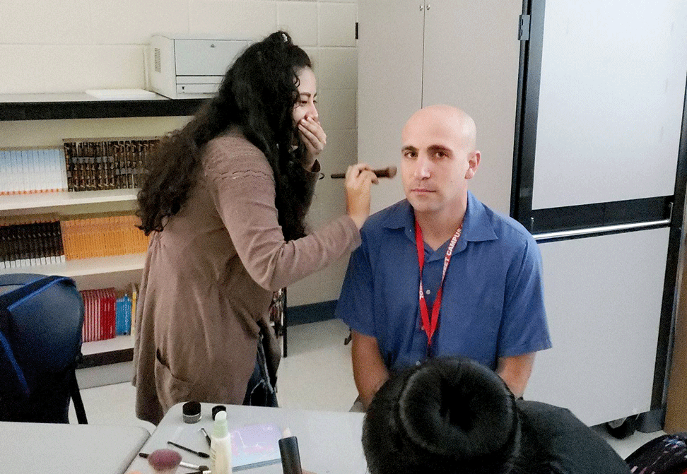student applies makeup to teacher Gabe Elias
