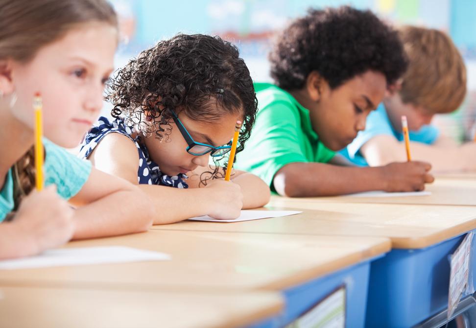 Multi-ethnic elementary school children writing in classroom.